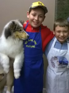 Two juniors wearing their grooming aprons holding a blue merle collie puppy.
